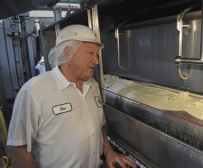 Joe Hines watches over the machine that makes the cheese curds at Ellsworth Cooperative Creamery, where he has worked for 51 years and is currently the plant superintendent.  PHOTO BY KRISTA KUZMA