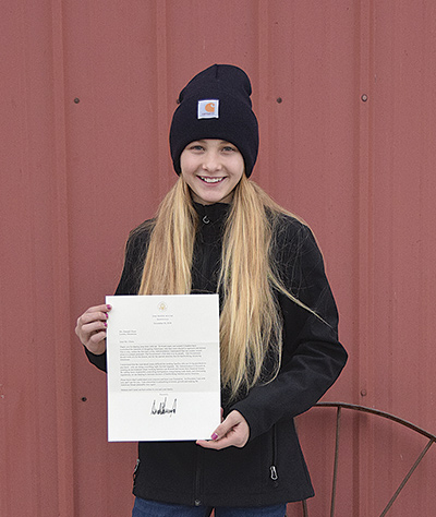 Hannah Olson holds the letter President Trump wrote her in response to her concern over current milk prices. Her parents, Carl and Heather, milk 55 cows near Hanover, Minn.  PHOTO BY DANNA SABOLIK