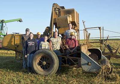 The Wuertz family – (from left) Luke, Brooke, Jim, Lisa, Peter, Paul and Tom – stand around a 1955 pull-behind combine Aug. 8 near their dairy and crop farm in Spring Hill, Minn. The family combined and baled 27 acres of oats using the older equipment.  PHOTO BY DANNA SABOLIK