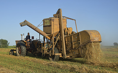 Brooke Wuertz pulls a 1955 Minneapolis Moline combine behind a tractor Aug. 8 on her family's farm near Spring Hill. The equipment has been in her family for four generations.  PHOTO BY DANNA SABOLIK