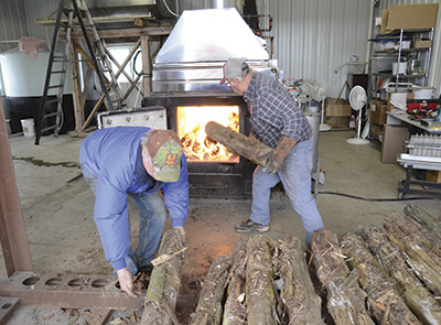 Ed (left) and Ken Staats add wood to the evaporator March 16. Sap is cooked at high temperatures over a wood-burning fire, which turns it into maple syrup. The firebox is filled with wood about every 20 minutes during the cooking process. PHOTO BY STACEY SMART